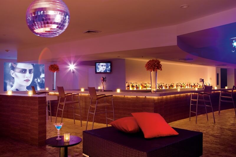 bar interior with disco ball, big screen and high stools