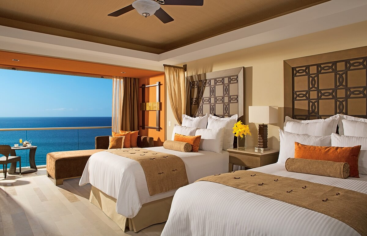 hotel room interior with two double beds and ocean view