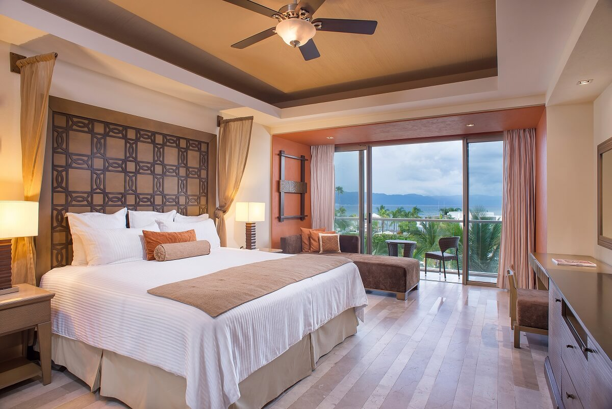 hotel room interior with king bed, and a balcony with ocean view
