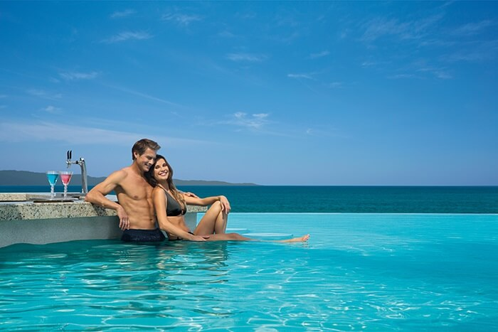 couple with cocktails in the infinity pool at now amber resort in puerto vallarta