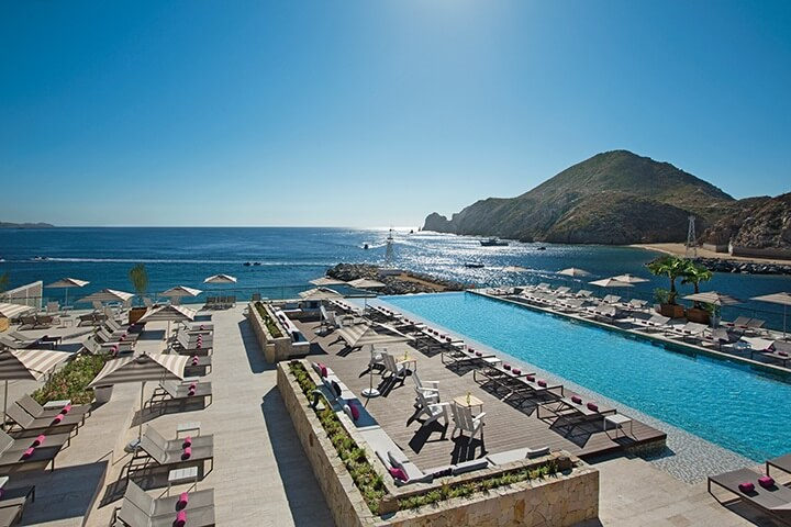 infinity pool and deck area with loungers overlooking the bay in cabo san lucas
