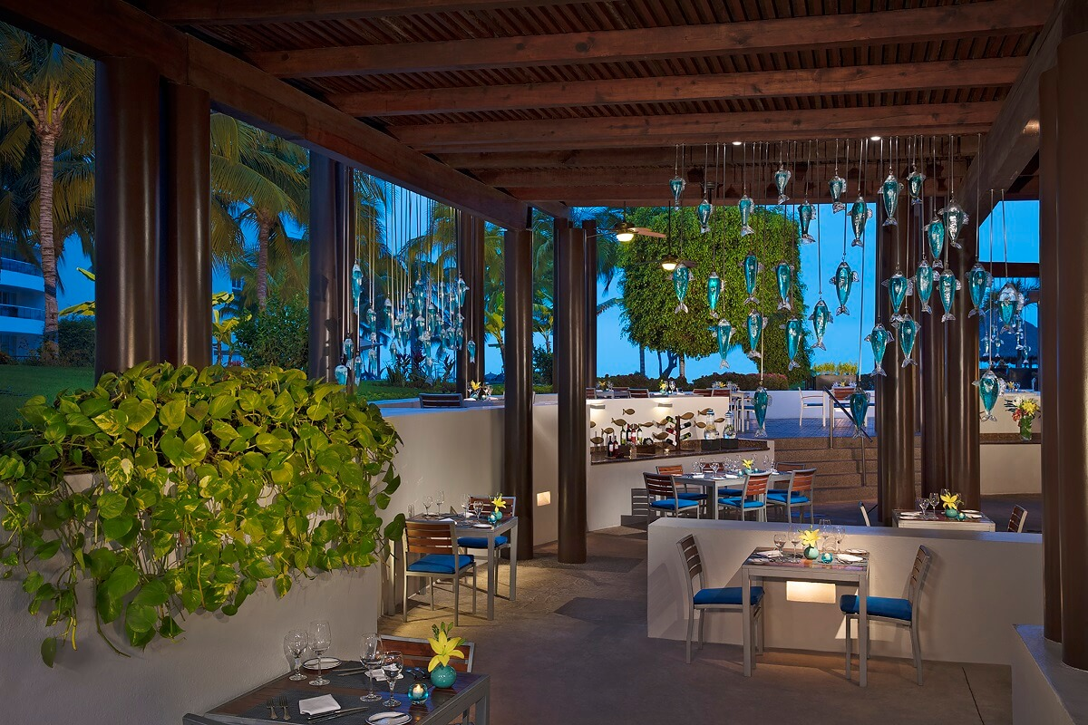 oceana restaurant with garden views, plants and glass fish hanging from the ceiling