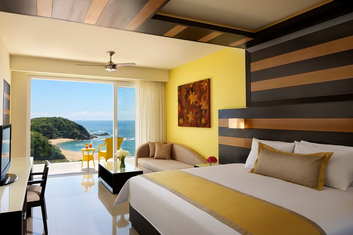 interior of a hotel room with a king bed, sofa and full ocean view secrets huatulco