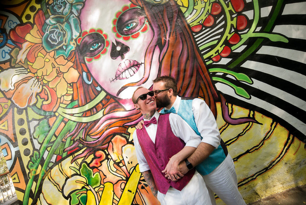 groom and groom in front of a colorful mural of a catarina