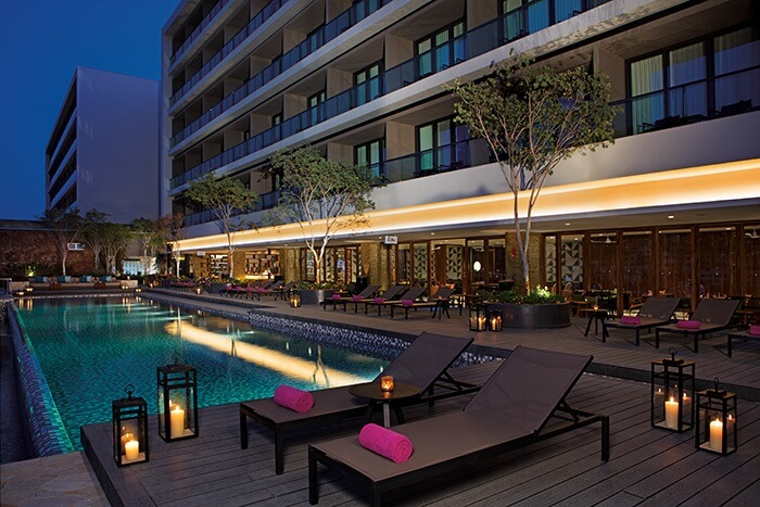 swimming pool area at dusk with lanterns and loungers