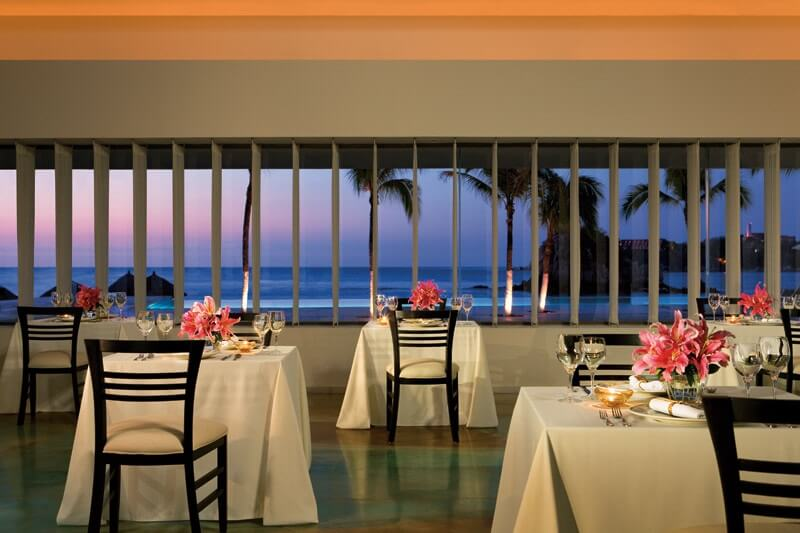 ocean view restaurant with tables for two set with lily flower centerpieces