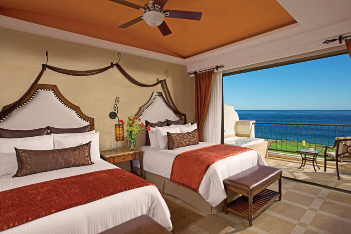 room with two double beds and a terrace with jacuzzi tub and ocean view