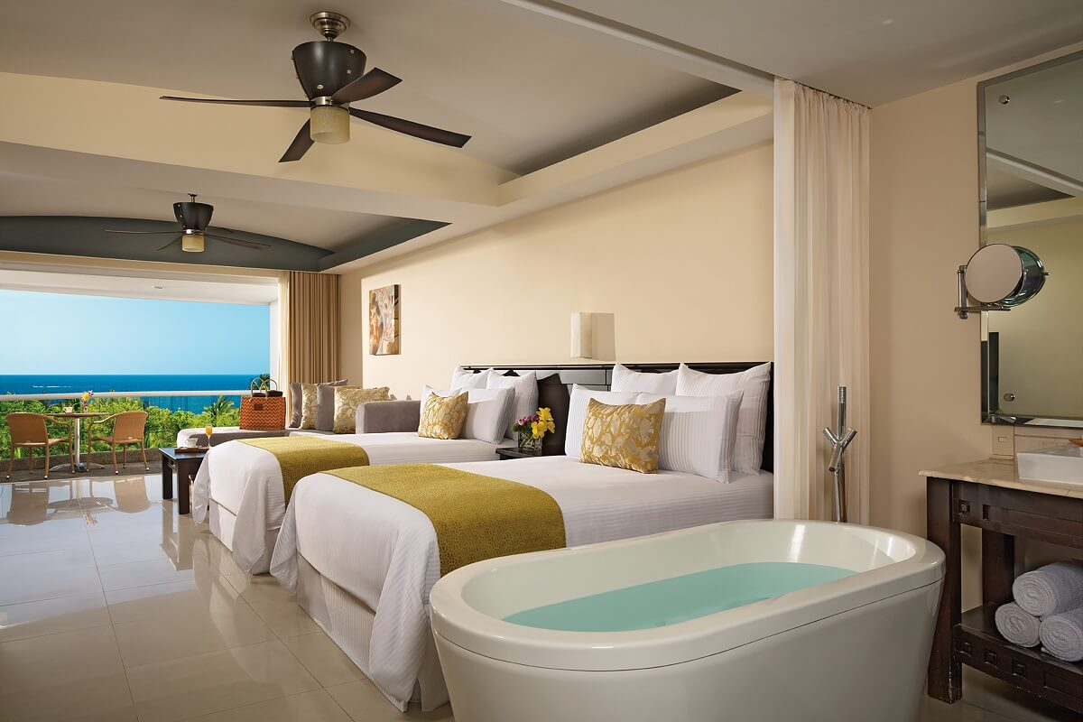 hotel room interior with two beds, a bathtub and a balcony with ocean views