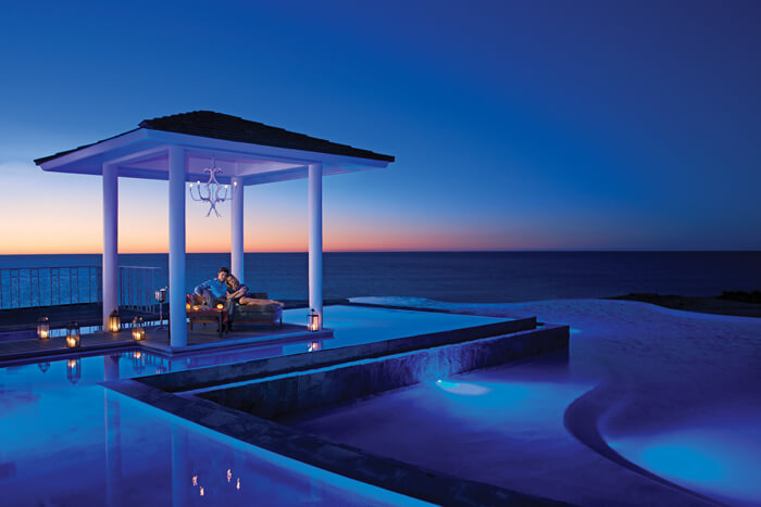 couple having a romantic dinner in an poolside area next to the ocean at Secrets Los Cabos