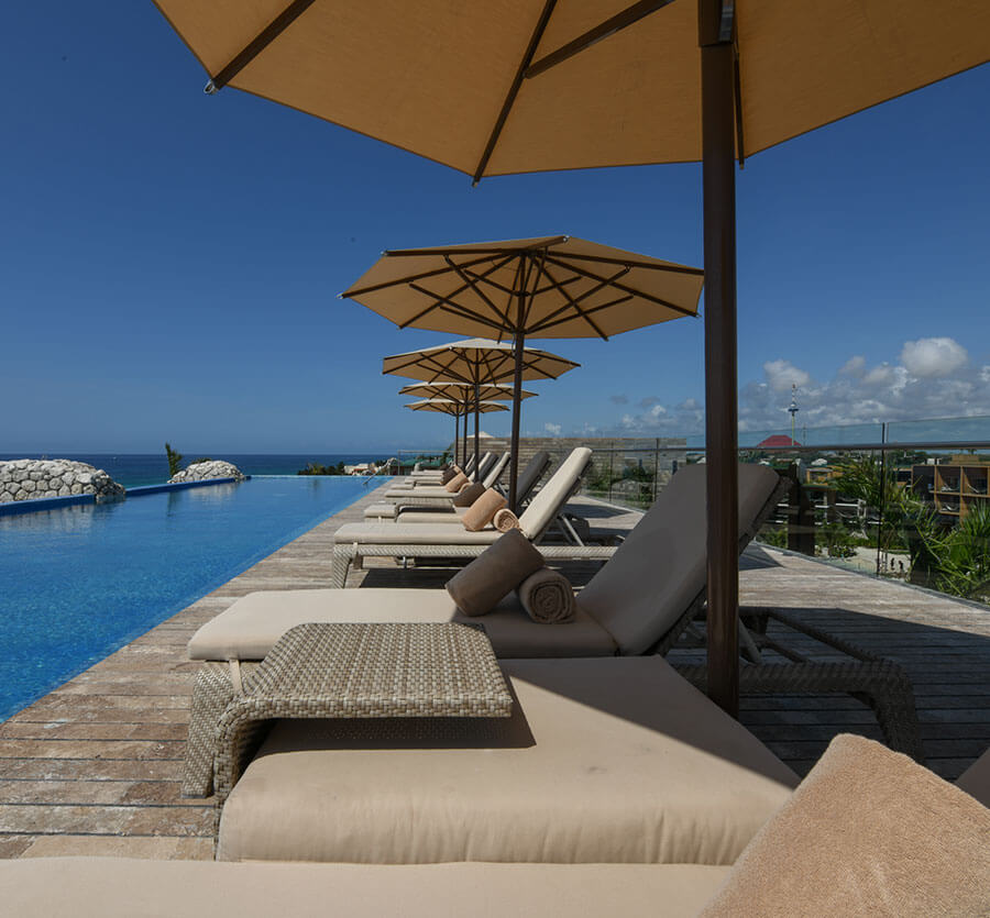 sky bar with loungers, parasols and an ocean view swimming pool hotel xcaret