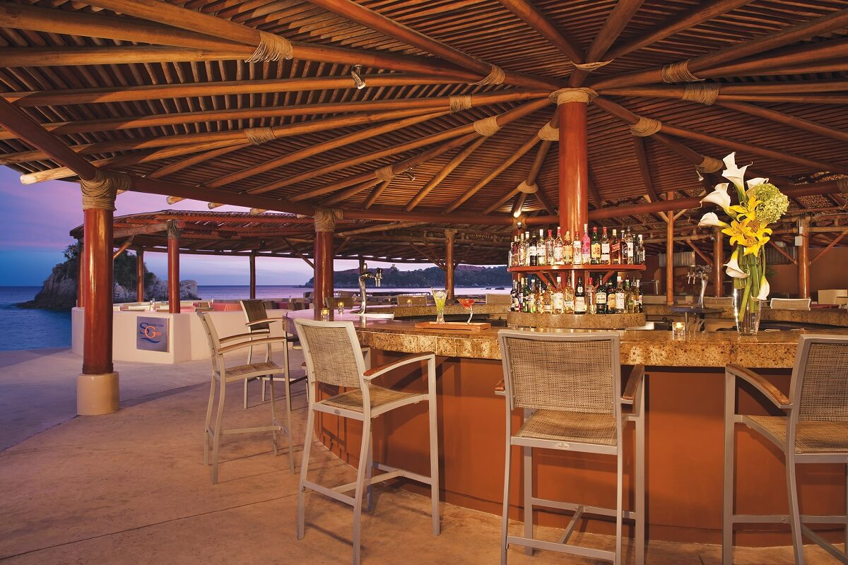 bar area with high stools and an ocean view at dreams huatulco