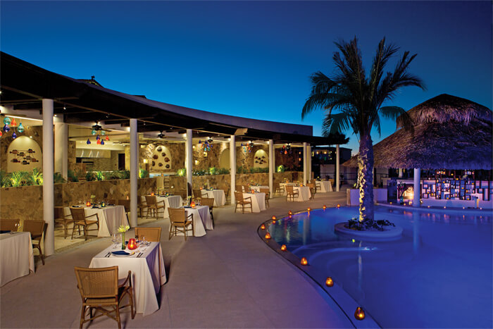 restaurant terrace with tables for two by the pool at Secrets Los Cabos