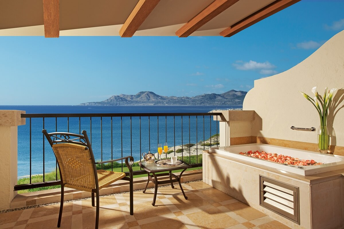 balcony with ocean view furnished with a chair, table and a jacuzzi drawn with rose petals