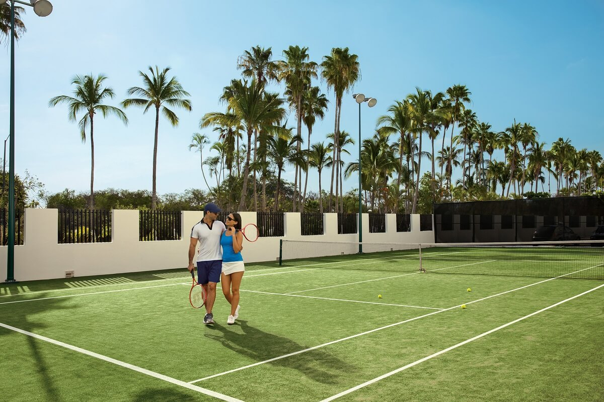 couple on tennis court surrounded by palm trees