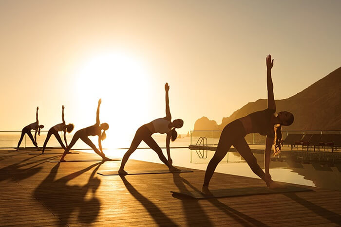 5 people in a yoga pose on a deck at sunrise