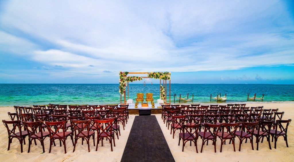 atelier weddings on the beach with an elevated ceremony platform and crossback wooden chairs
