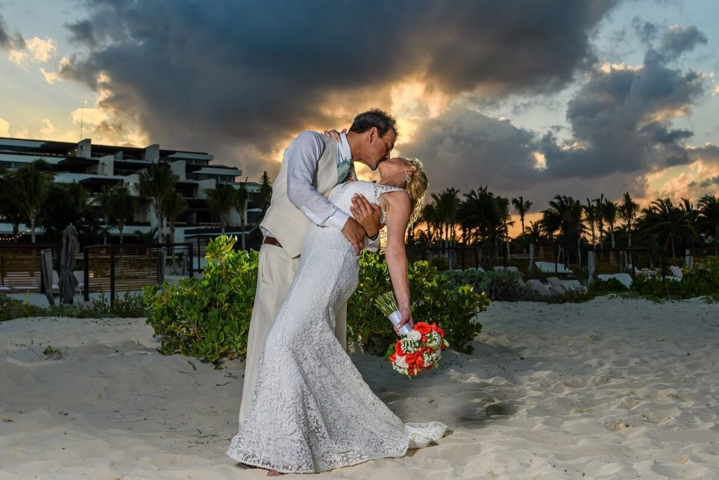 groom dipping his bride for a kiss on the beach after their wedding at atelier playa mujeres