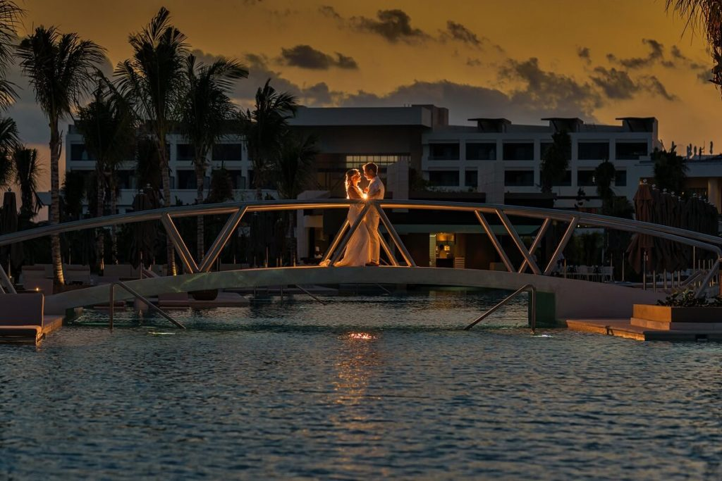 newlywed couple kissing a on a bridge over the pool at atelier hotel