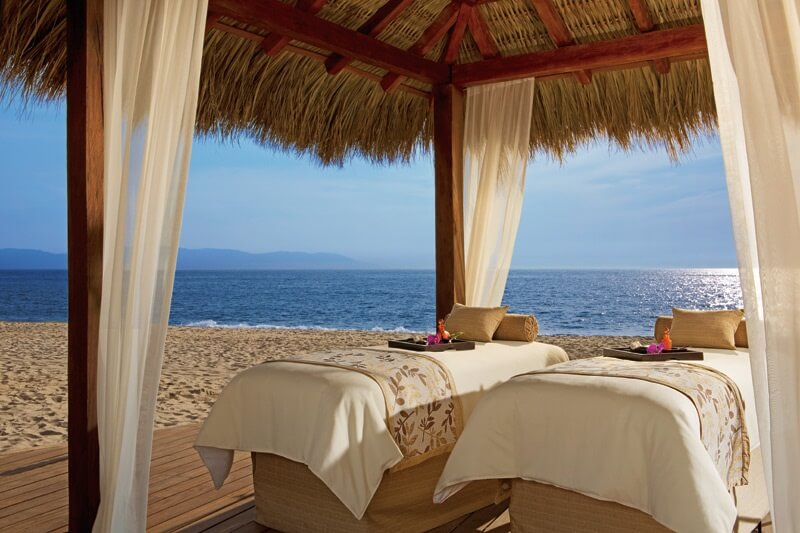 double massage on the beach under a thatch roof