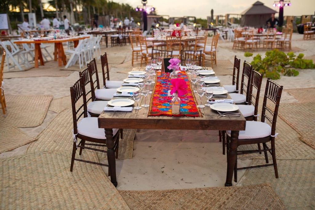 beach wedding reception with colorful runner on wooden table at atelier hotel