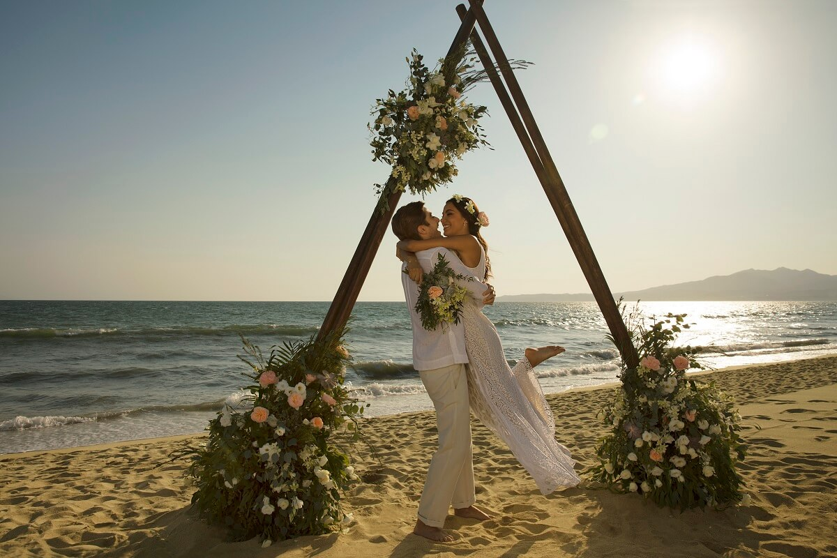 Reflect Nuevo Vallarta wedding couple on the beach with teepee arch and florals