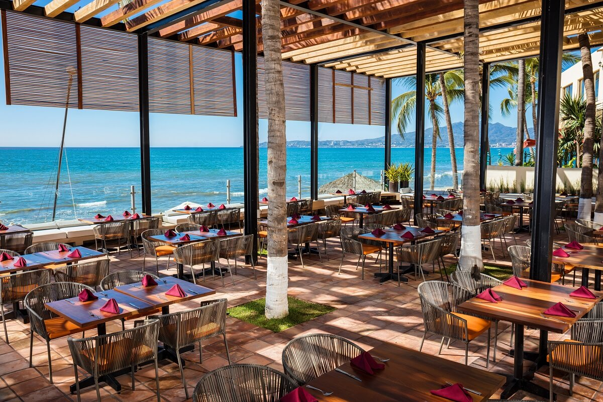 beachside open air restaurant with square wooden tables