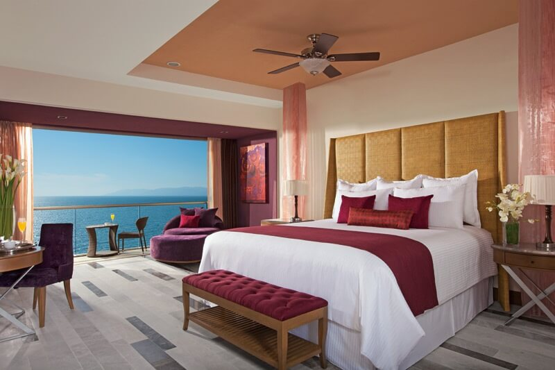 hotel room with king bed and balcony with ocean view