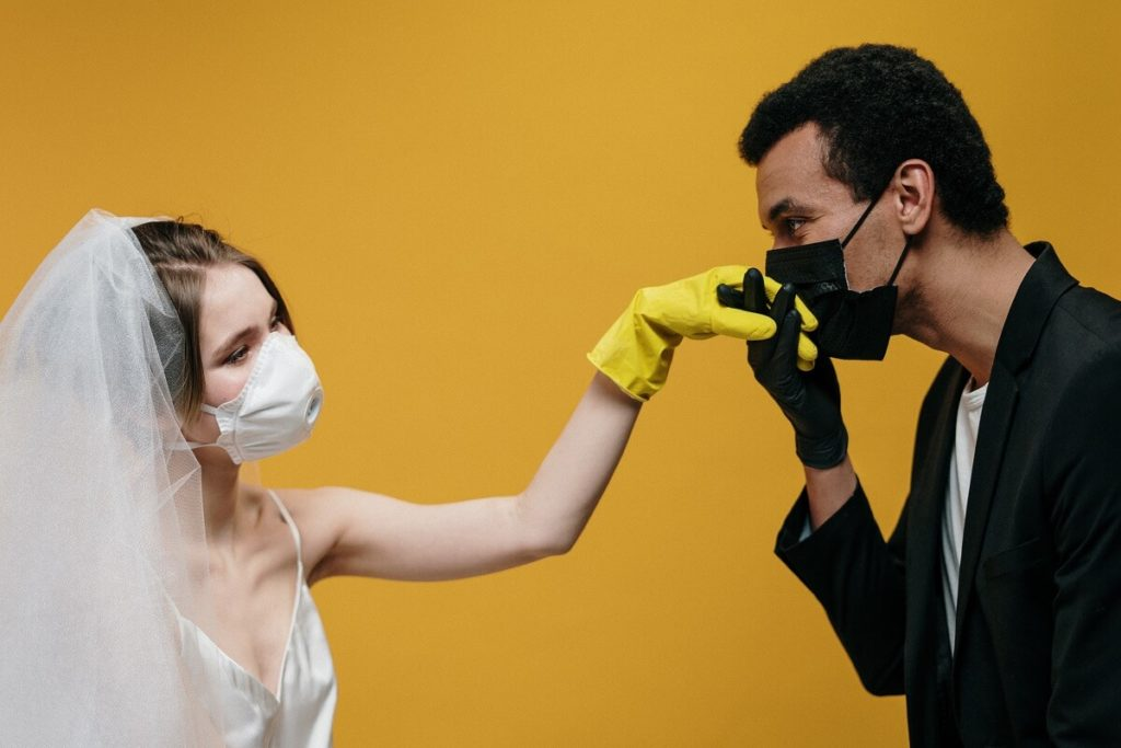 groom with face mask kissing bride's hand