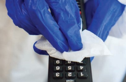 gloved hands disinfecting remote