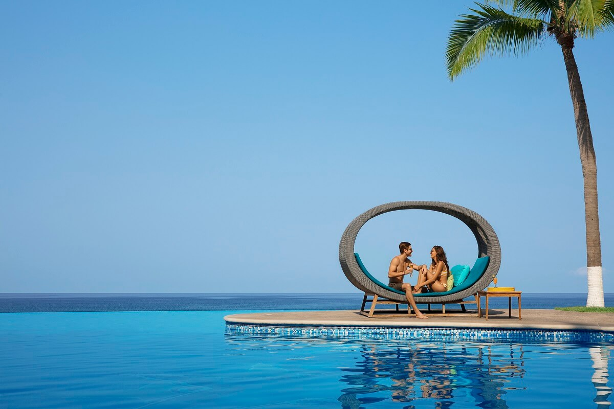 couple in circular lounger by the infinity pool at Reflect Nuevo Vallarta