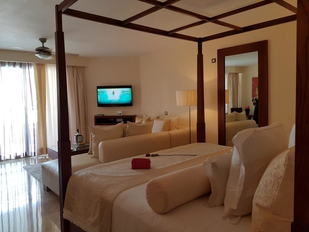 hotel room interior with king 4 poster bed and integrated living room area