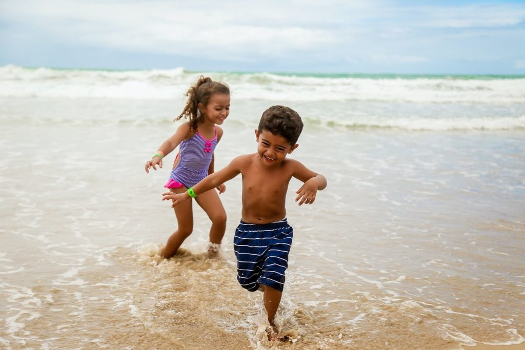 boy and girl playing in the ocean