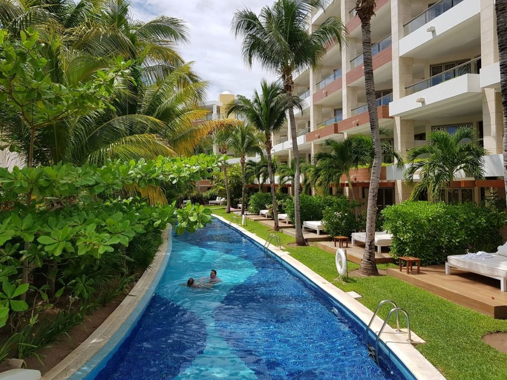 lazy river with vegetation on the left and the excellence playa mujeres rooms on the right