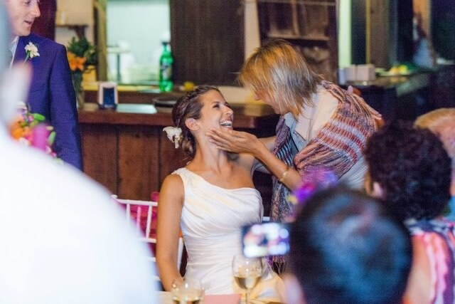 wedding planner cradling bride's face with affection