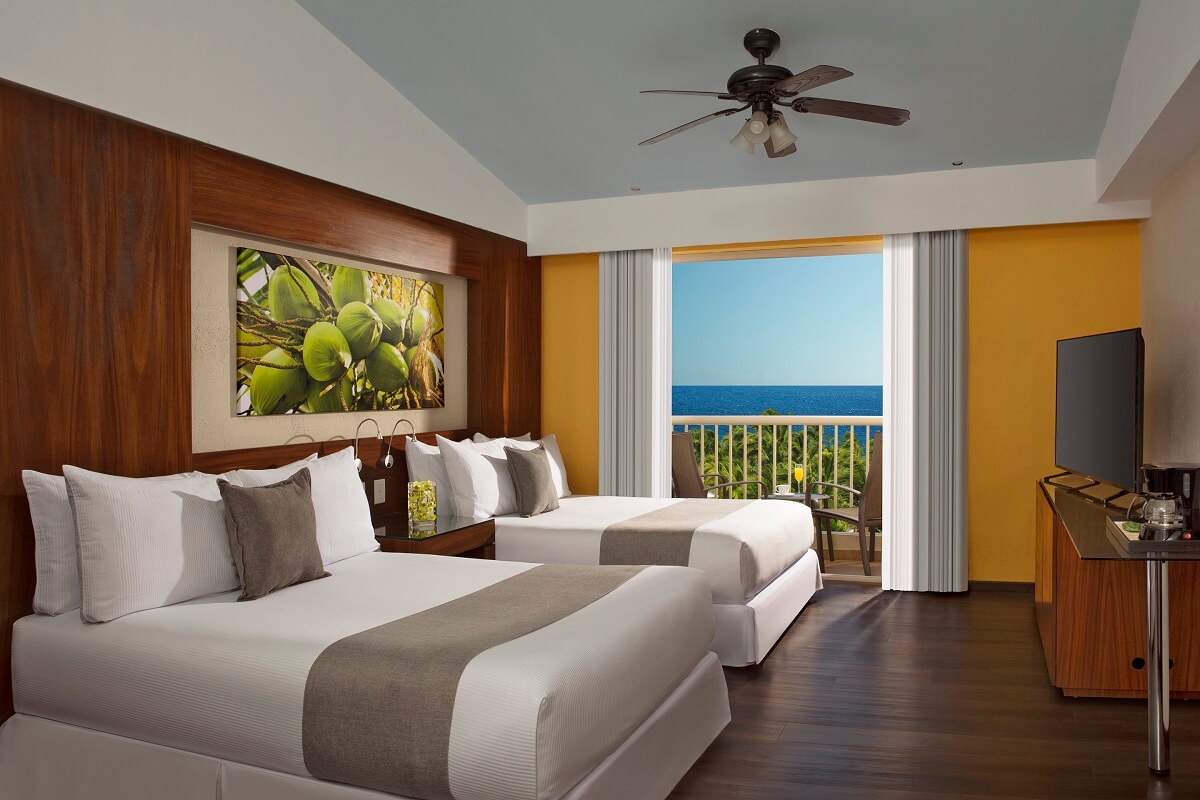 hotel room interior with two double beds and an ocean view balcony