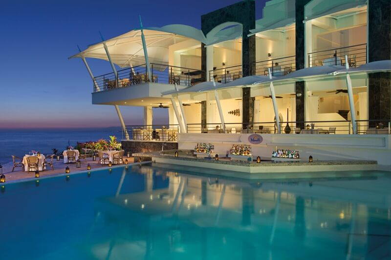 swimming pool at dusk with view of bar, restaurant and beach at secrets vallarta bay