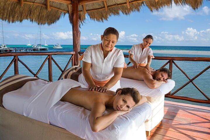 couples massage in outdoor hut over the ocean