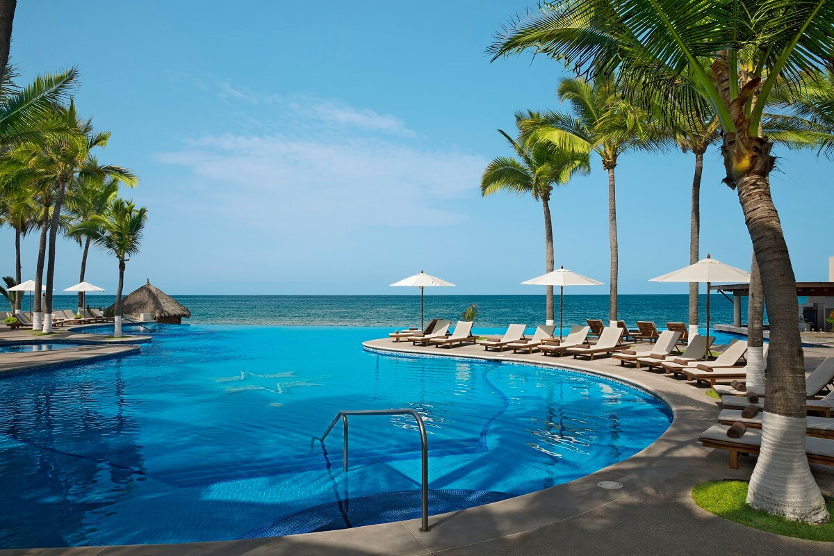 deserted infinity pool with loungers, palm trees at Reflect Nuevo Vallarta