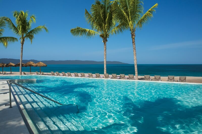 swimming pool with view of palm trees, ocean and mountains in the distance
