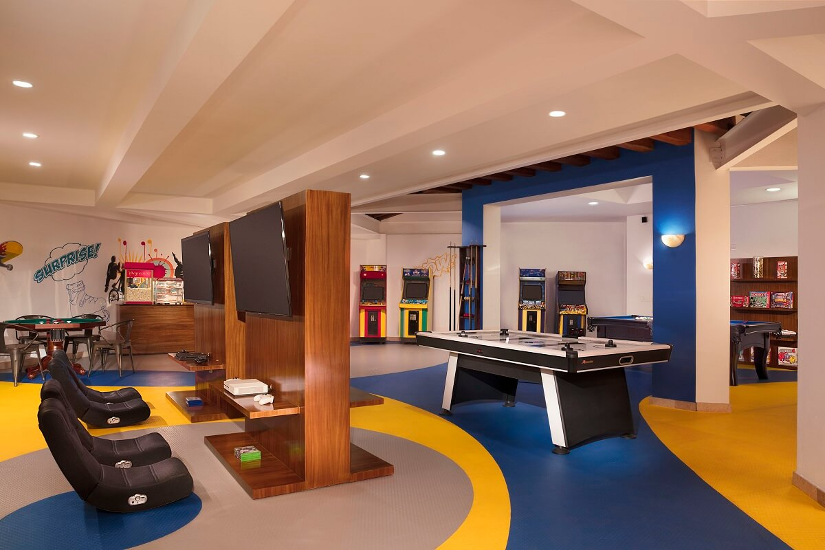 teen club area with video game consoles, air hockey and geometric colorful floor