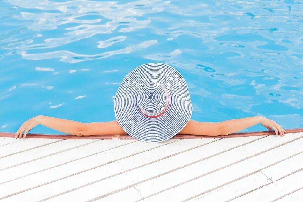 woman with wide brimmed hat leaning on the side of a swimming pool