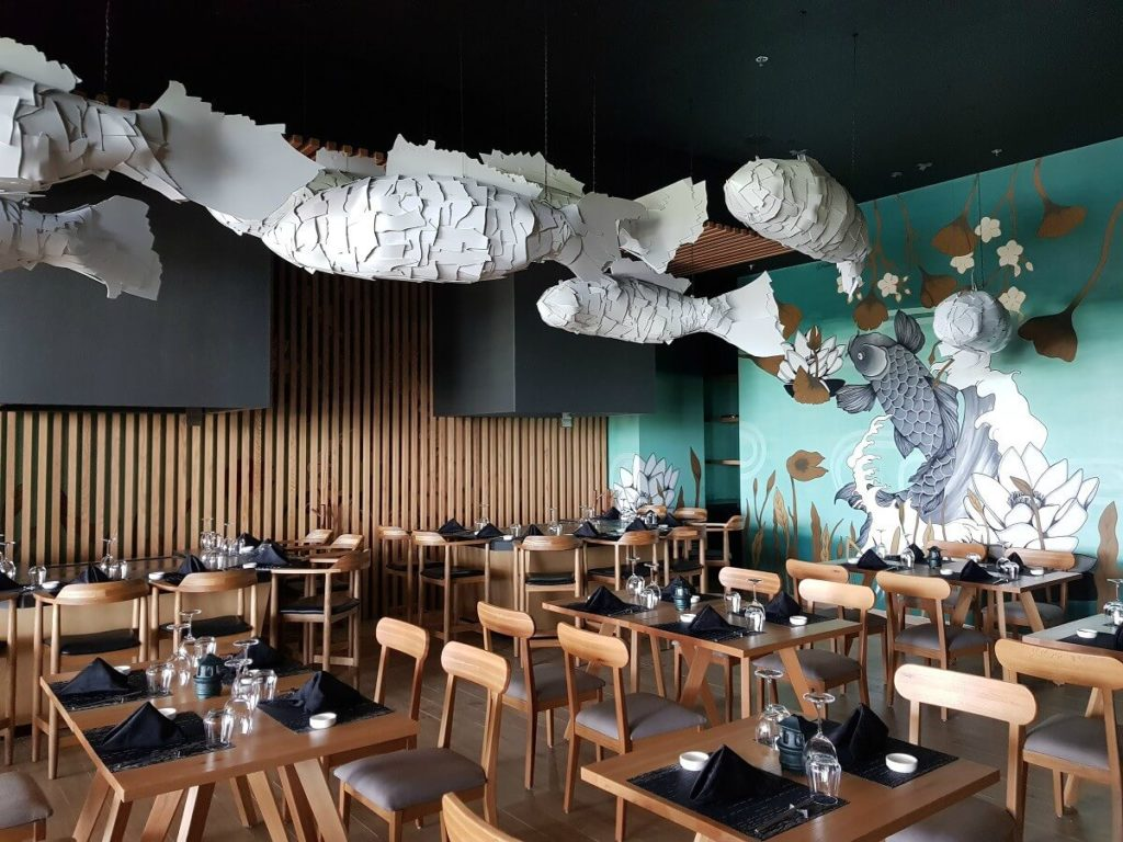 interior of asian restaurant with artistic hanging fish and wooden furniture