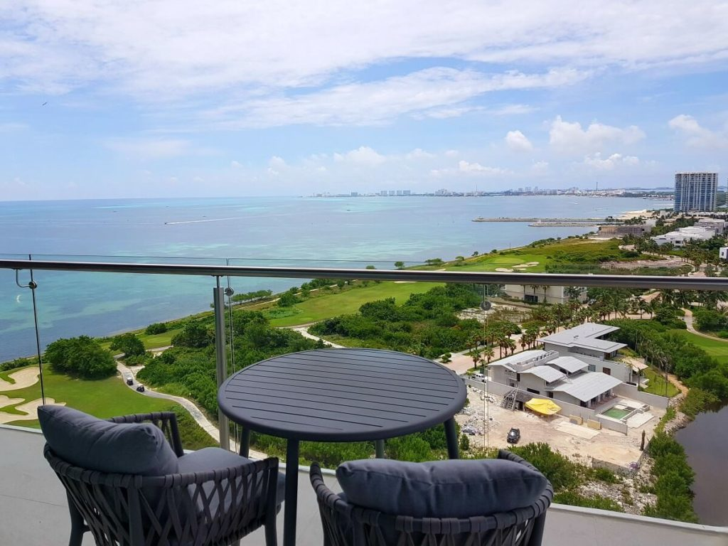 balcony with small table and two cushioned chairs dreams vista cancun