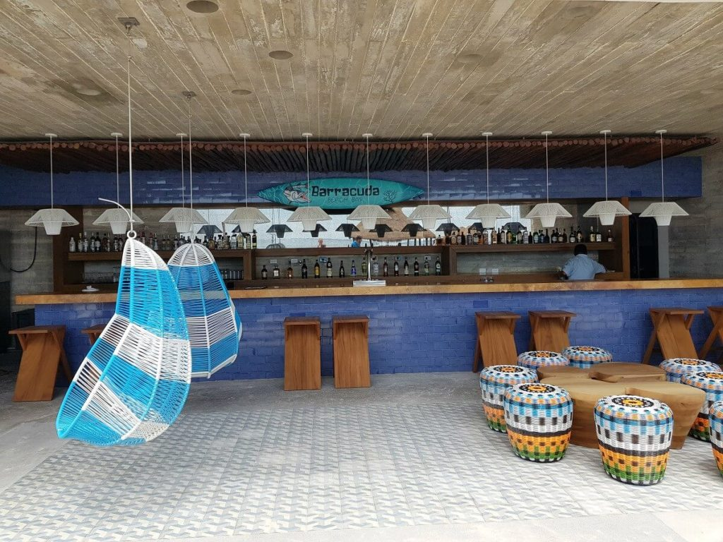 beach bar with hanging acapulco chairs and wooden stools