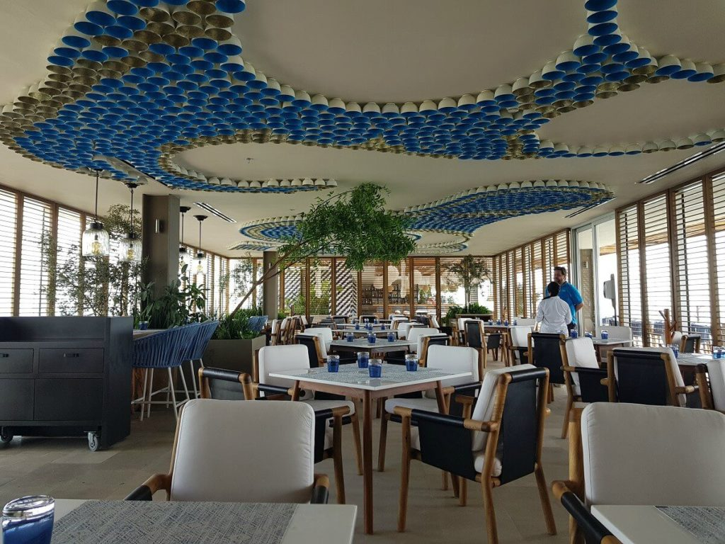 blue water grill restaurant interior with white and blue decor including ceiling art with bottles