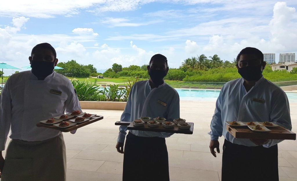 3 waiters with face masks serving bites at dreams vista cancun