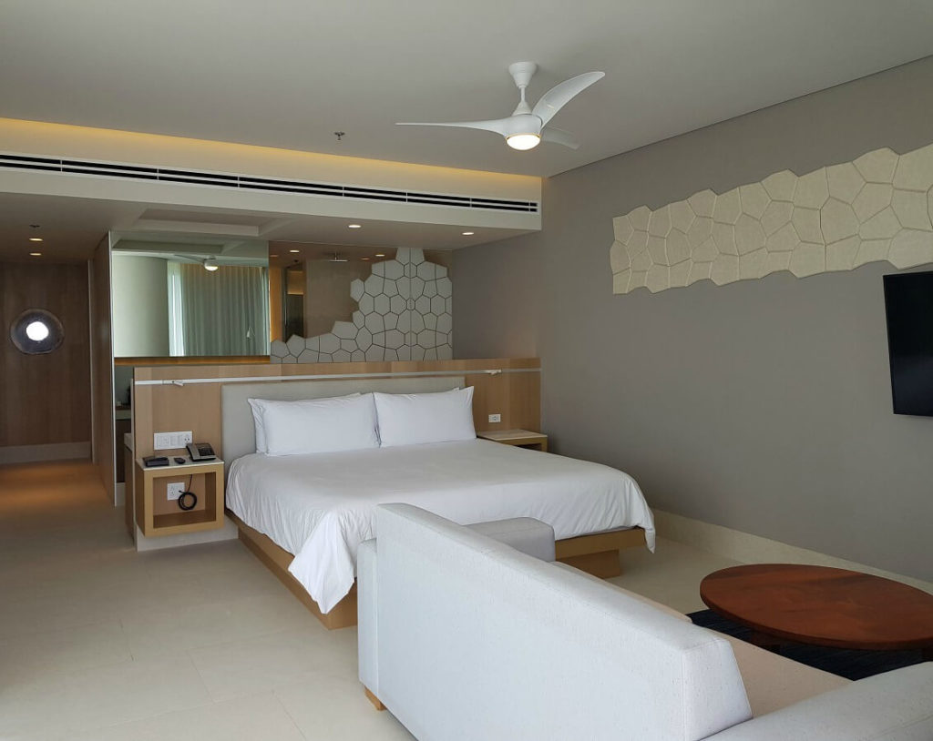 hotel room interior with lounge area and king bed