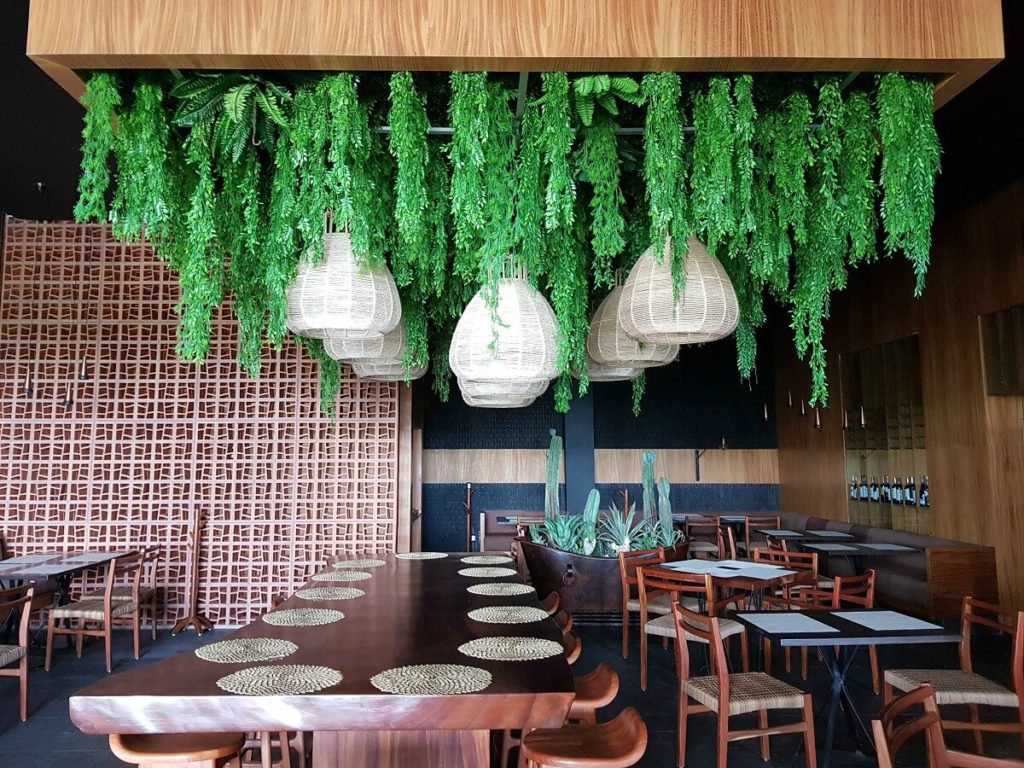 mexican restaurant interior at dreams vista cancun with hanging plants, wicker lights and hard wood table