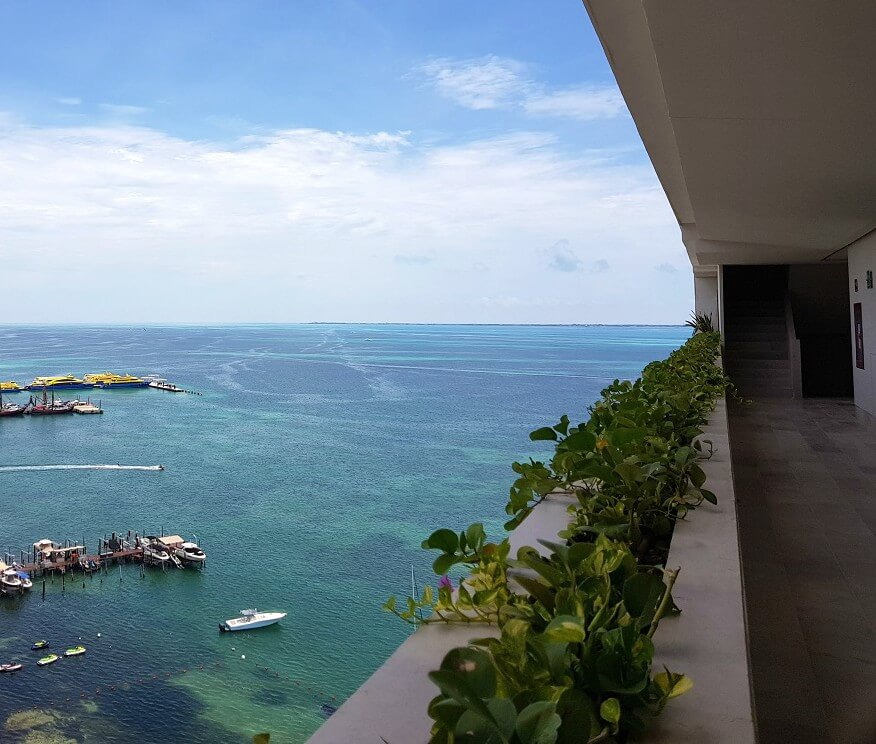 view of hallway, plants and ocean with boats at dreams vista cancun