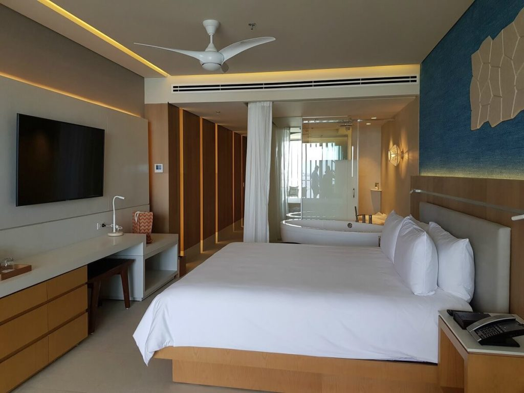 hotel room interior with king bed, double jacuzzi and modern decor